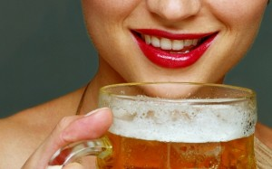 Young woman smiling, holding pint of beer, close-up Woman Drinking Beer